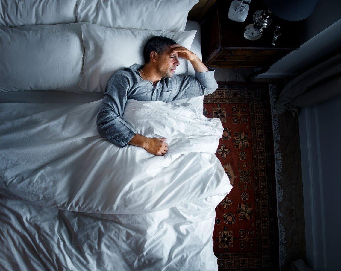 man-on-bed-with-a-headache-SGQKF9X