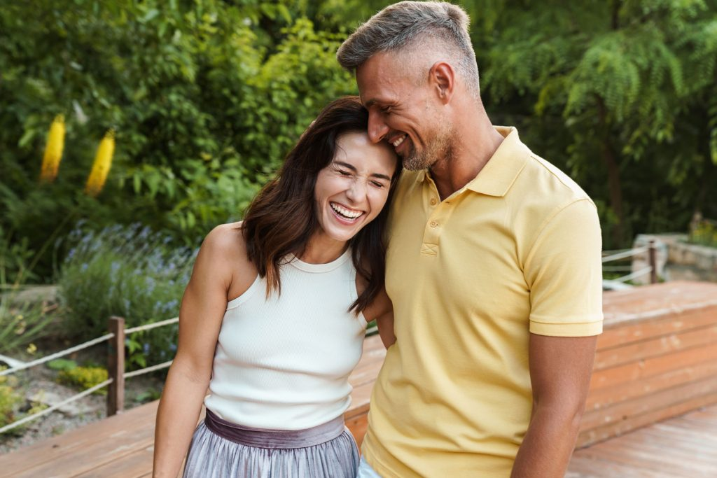 portrait-of-joyful-middle-aged-couple-aughing-and--UX4HB7A